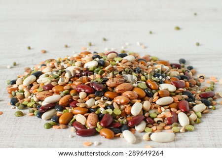 Dried mix of legumes and cereals on wooden table - stock photo