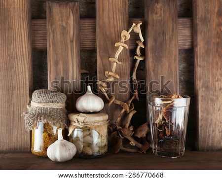 Dried mushrooms and glass bottles with marinated garlic and mustard on wooden planks background