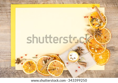 Dried oranges, cinnamon, cloves, cardamom, handmade milk chocolate in rustic packing, mulled wine on yellow and wooden background. Christmas, New Year and winter. Free space for your text. - stock photo