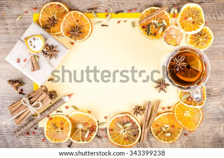 Dried oranges, cinnamon, cloves, cardamom, handmade milk chocolate with nuts, mulled wine, wooden pencil, list of paper on wooden background. Christmas, New Year and winter. Free space for your text. - stock photo