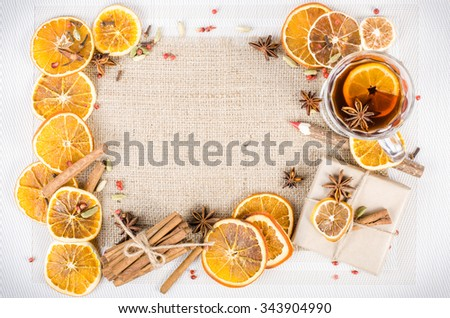 Dried oranges, cinnamon, cloves, cardamom, handmade milk chocolate with nuts, mulled wine, wooden pencil on sackcloth, canvas. Christmas, New Year and winter. Free space for your text. - stock photo