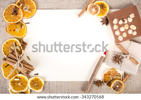 Dried oranges, cinnamon, cloves, cardamom, handmade milk chocolate with nuts, wooden pencil, list of paper on sackcloth, canvas. Christmas, New Year and winter. Free space for your text. - stock photo