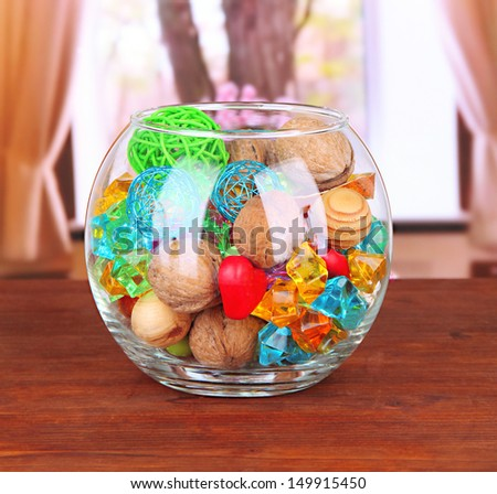 Dried oranges, wicker balls and other home decorations in glass bowl, on bright background - stock photo