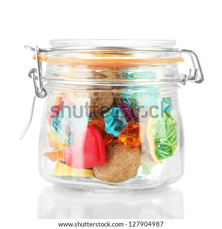 Dried oranges, wicker balls and other home decorations in glass jar, isolated on white