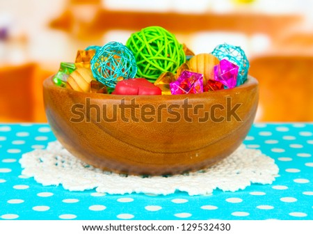 Dried oranges, wicker balls and other home decorations in wooden bowl, on bright background - stock photo