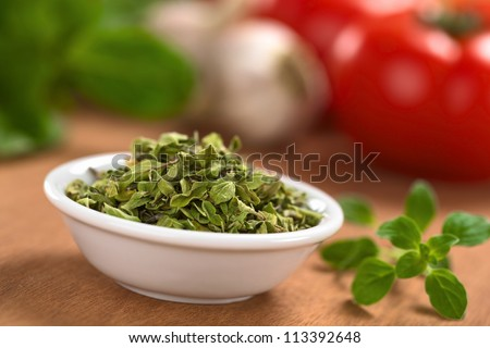 Dried oregano leaves in small bowl with fresh oregano on the side, tomato, garlic and basil in the back (Selective Focus, Focus one third into the dried oregano leaves) - stock photo