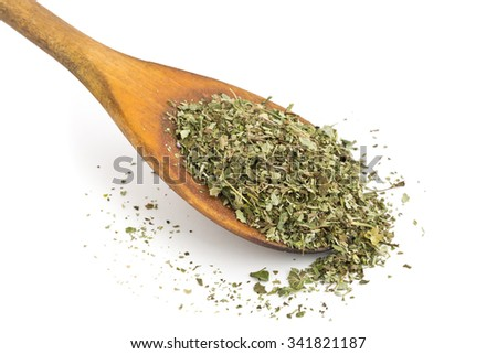 Dried oregano leaves on wooden spoon over white background