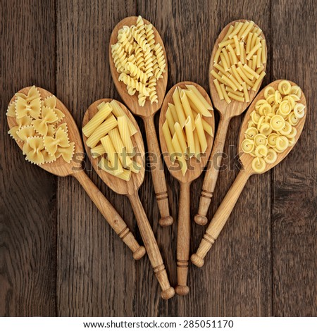 Dried pasta food selection in wooden spoons over old oak background. - stock photo