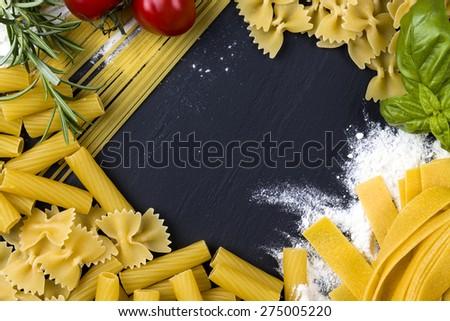 dried pasta on black stone background , pasta concept - stock photo