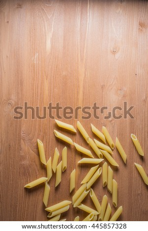 Dried pasta selection on wooden background.
