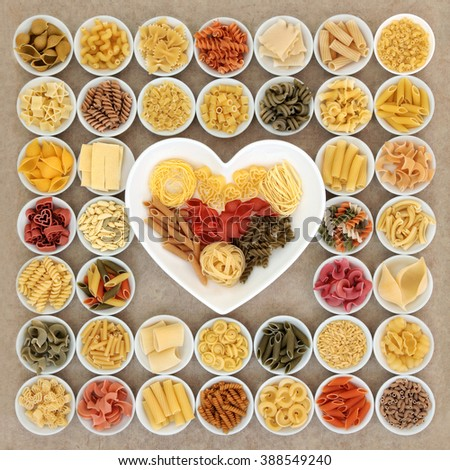 Dried pasta spaghetti food varieties in round porcelain bowls and heart shaped dish over natural hemp paper background. - stock photo