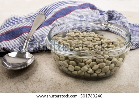 dried peas in a glass bowl with cold water