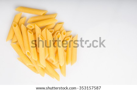 Dried penne regate pasta or cylinder shaped pasta over white background