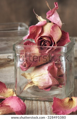 Dried pink roses heads in glass jar and petals on rustic wooden table. Shallow DOF. - stock photo
