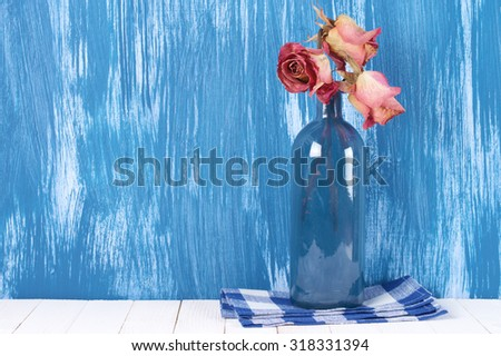 Dried pink roses in blue glass bottle with napkin against blue rustic painted wall. - stock photo