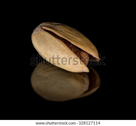 Dried pistachio with reflection on the black background - stock photo