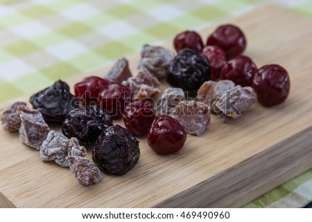 Dried plums on wooden plate.