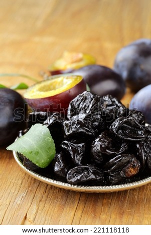 Dried plums prunes and fresh berries on the wooden table - stock photo