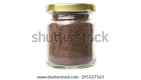 Dried processed tea leaves in a mason jar over white background