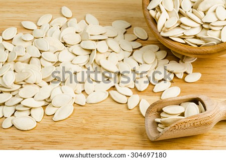 dried pumpkin seeds, on wooden background - stock photo