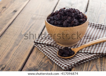 Dried raisins in wooden cup and spoon on wooden table. - stock photo