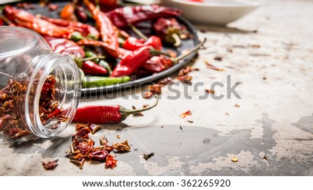 Dried red Chili peppers on a tray and in the jar. On rustic background. - stock photo