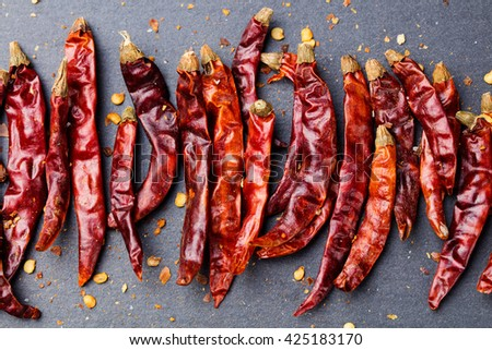 Dried red chili peppers on slate background Top view Copy space - stock photo