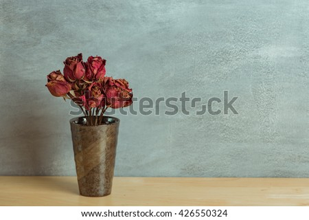 Dried red rose in cup on wood table - stock photo