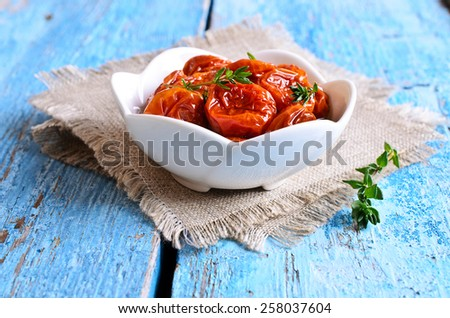 Dried red tomatoes in oil with branches of thyme - stock photo