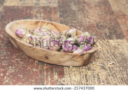 Dried rosebuds. Pretty little edible violet  rose buds, on old wooden table . Macro photograph with  very shallow depth of field. Done with a vintage retro filter  - stock photo