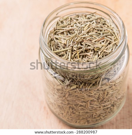 Dried rosemary herb leaves in a mason jar on wooden board