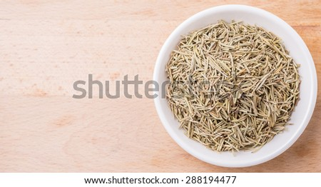 Dried rosemary herb leaves in white bowl over wooden background