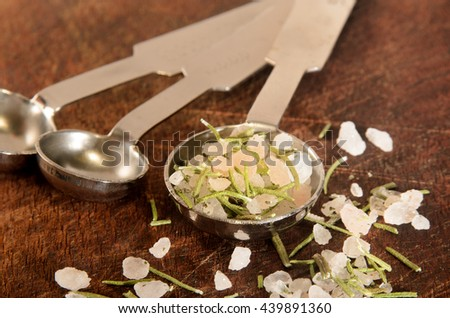 dried rosemary with coarse sea salt on a measurement spoon - stock photo