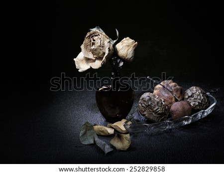 Dried roses in heart shape bottle and rotten fruits light painting still life art