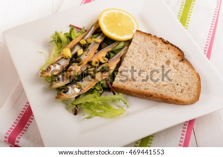 dried stint on salad with garlic and parsley, a slice of bread and lemon on a plate