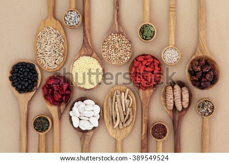 Dried super health food selection in wooden spoons over natural paper background. High in antioxidants, minerals, vitamins and dietary fiber. - stock photo