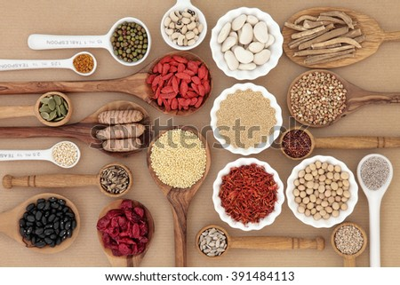 Dried superfood selection in spoons and bowls over natural paper background.