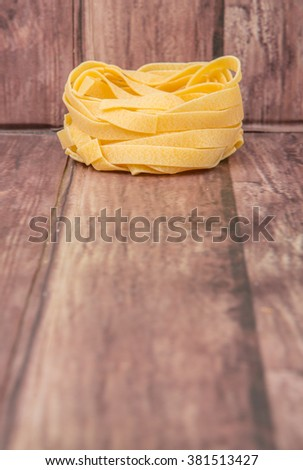 Dried tagliatelle pasta or ribbon shaped pasta or nest shape pasta over wooden background