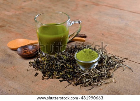 Dried tea leaf and powder with glass on wood.