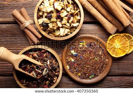 Dried tea leaves, fruits and cinnamon sticks - stock photo