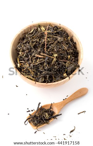 Dried tea leaves in wooden bowl with wooden spoon on white background