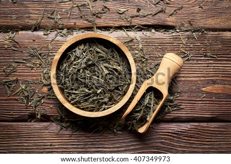 Dried tea leaves on wooden background