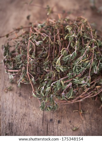 Dried thyme leaves and stems on a wooden desk - stock photo