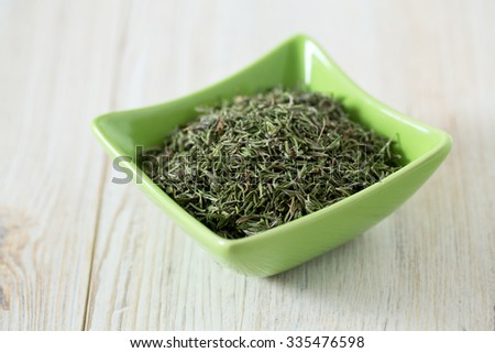 dried thyme on wooden surface - stock photo
