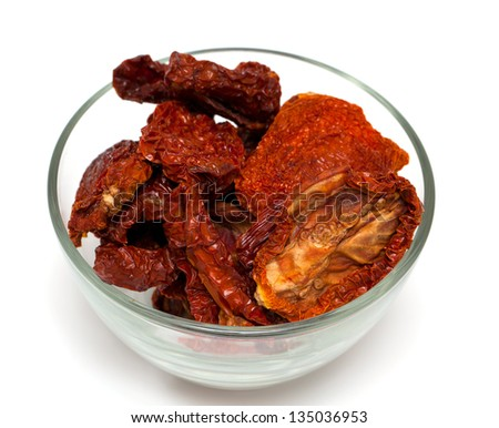 dried tomatoes in a glass bowl isolated on white background