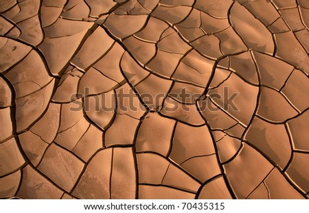 Dried up and cracked mud in a river bed - stock photo