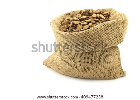 dried watermelon seeds in a burlap bag on a white background