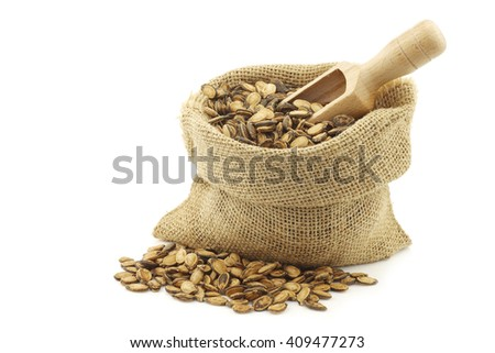 dried watermelon seeds in a burlap bag with an wooden scoop on a white background
