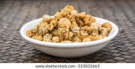 Dried white mulberry in a white bowl over wicker background