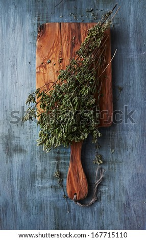 Dried wild oregano on a kitchen board - stock photo